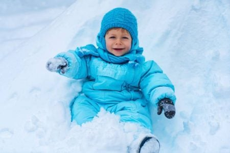 Smiling toddler in a snowsuit playing in the snow