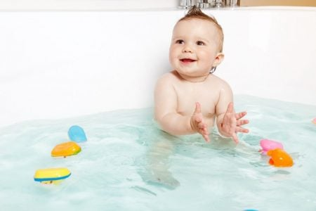 Cute baby playing with bath toys in the tub