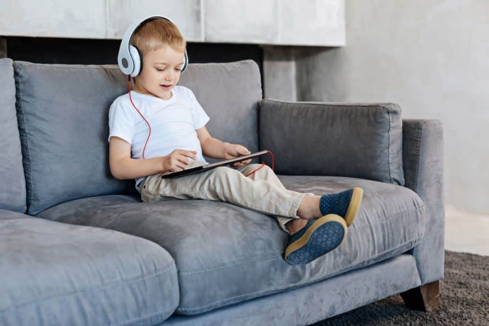 Kid wearing headphones while playing with ipad