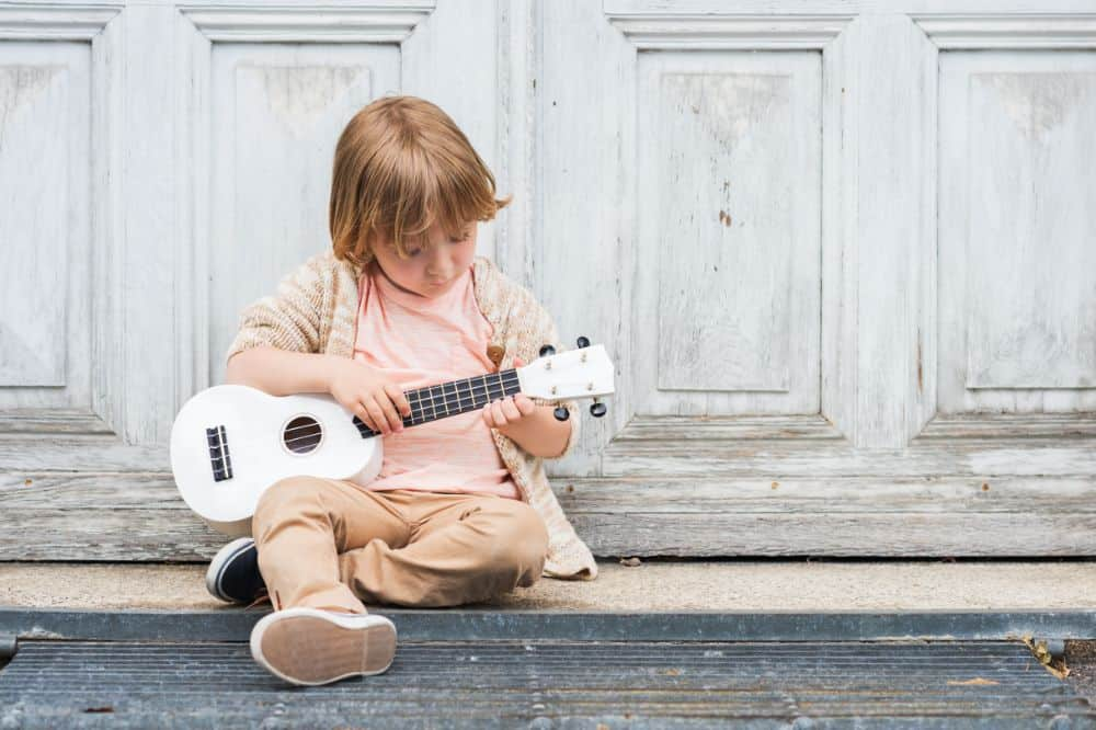 Little boy playing the ukelele