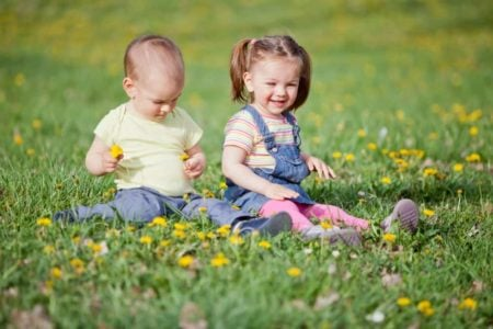Smiling children sitting on the grass