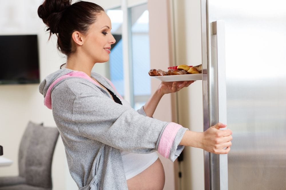 Pregnant woman taking food from the fridge