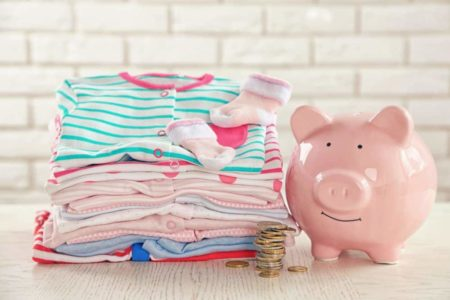A pile of baby clothes and a piggy bank