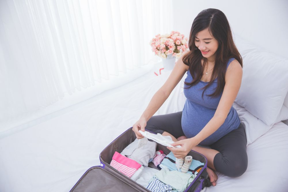 Pregnant woman organizing clothes