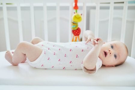 Baby lying on her back in a crib