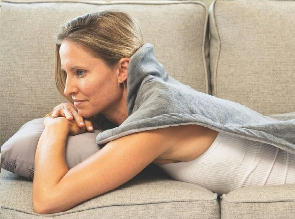 Woman lying on sofa with heating pad on her back