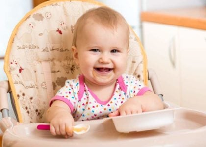 Smiling baby girl eating in a high chair