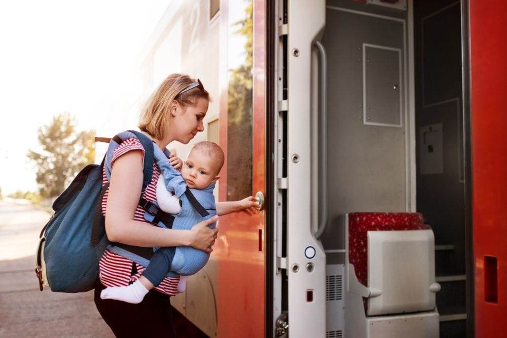 Mom boarding a train while wearing her baby in a carrier