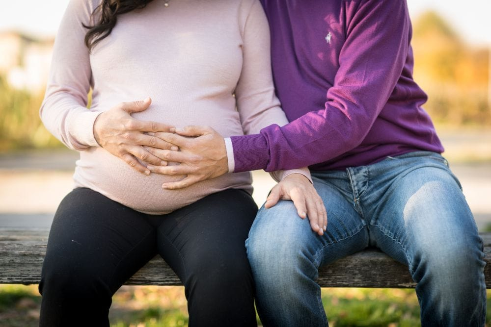 Couple sitting on a bench and holding woman's pregnant belly