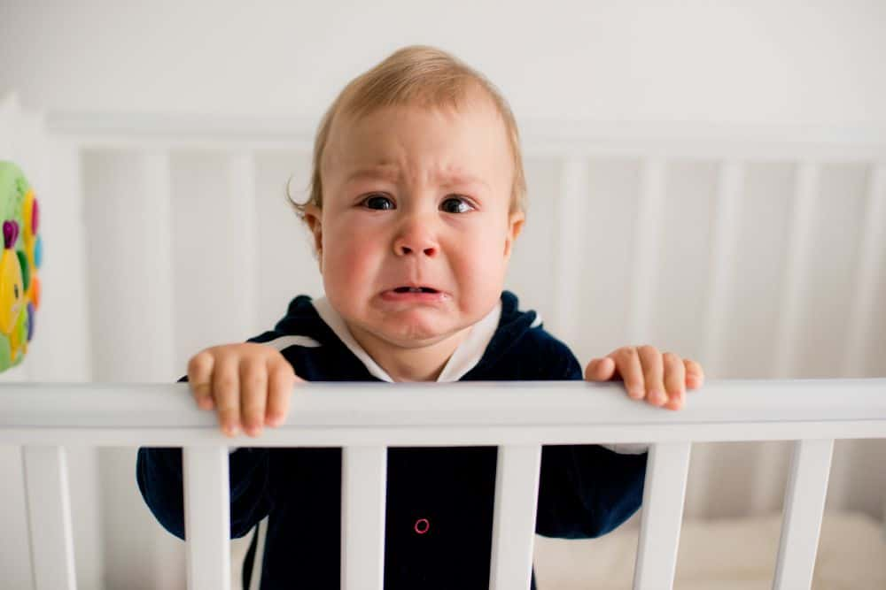 Baby boy crying in his crib
