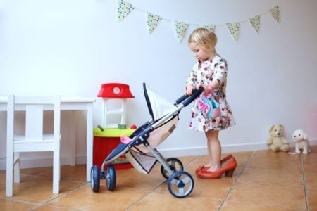 Little girl in heels pushing a doll stroller