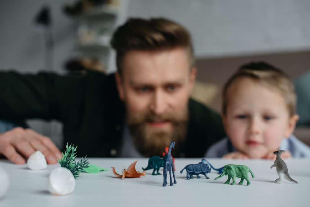 Father and son playing with dinosaur toys