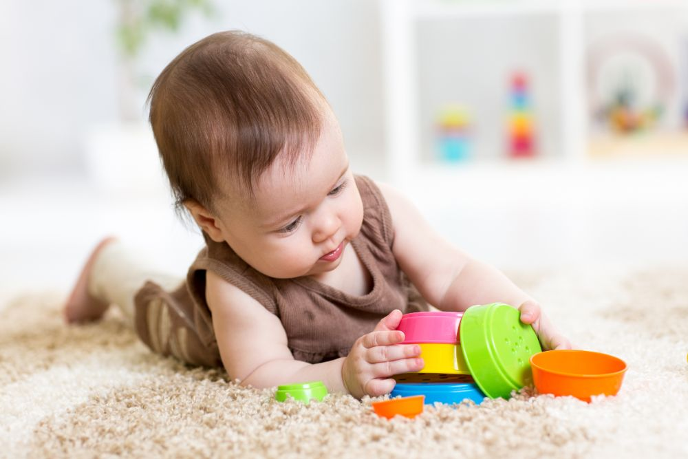 Baby girl playing with stacking toy