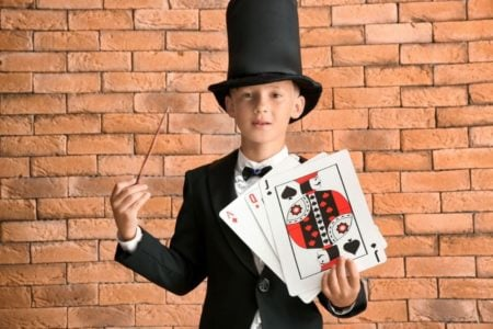Young magician holding a wand and deck of cards
