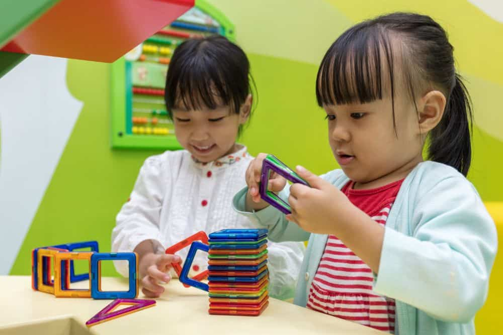 Asian children playing with magnetic toys