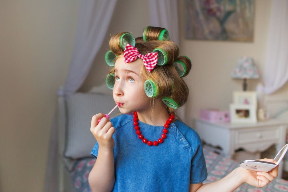Little girl with hair in curlers putting on lip gloss