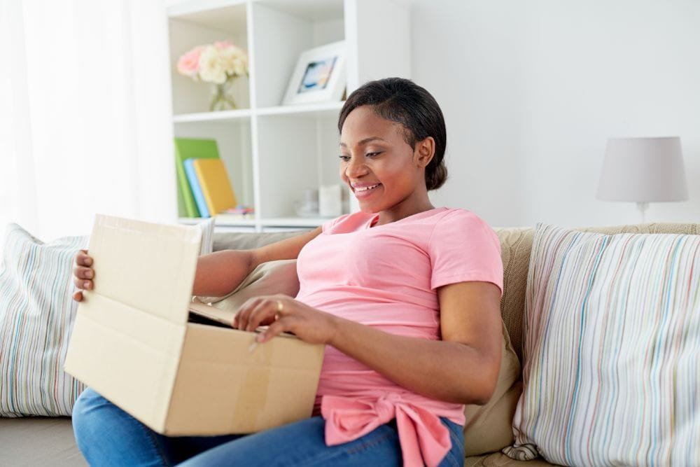 Pregnant woman smiling while opening a gift box