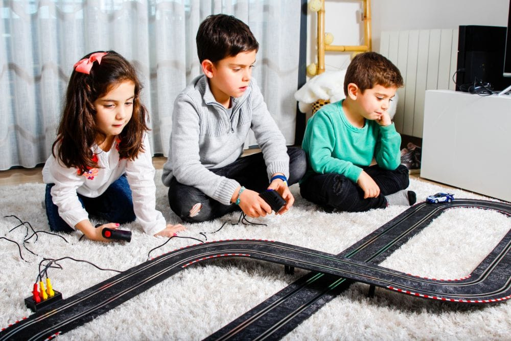 Three children playing with race track