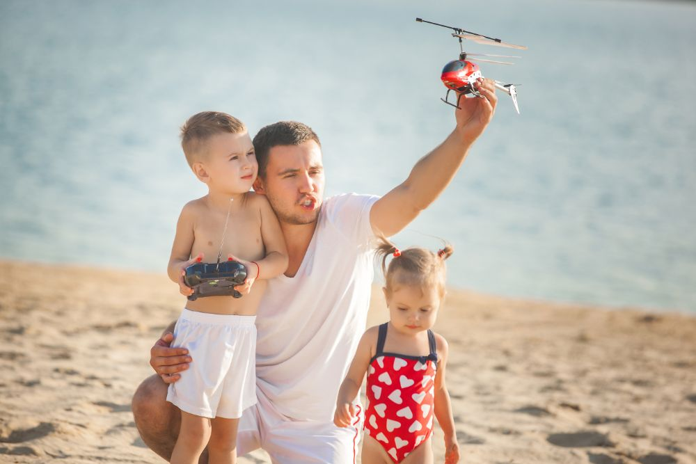 Father playing with RC helicopter at the beach with children