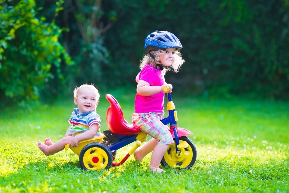 Toddler riding a bicycle with baby brother