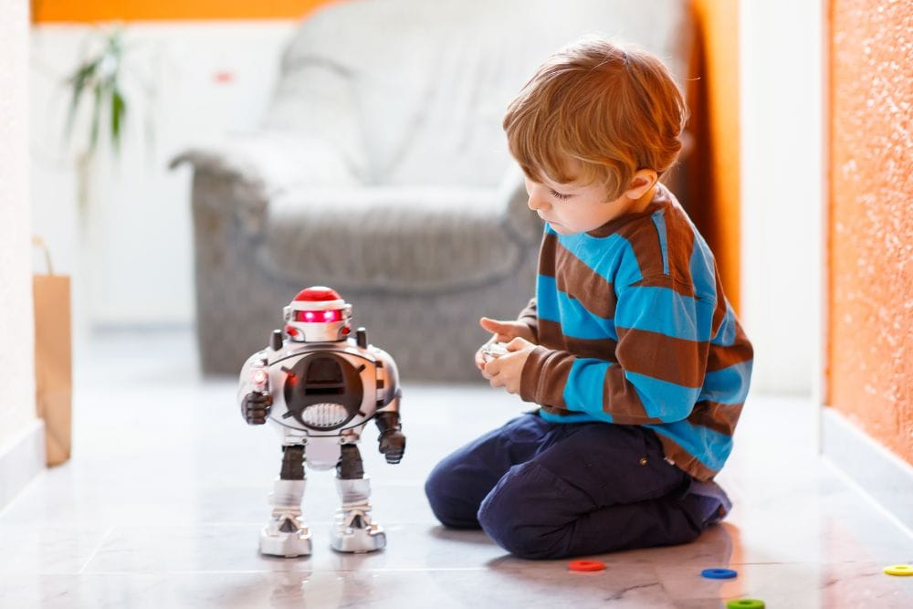 Little boy playing with a robot toy