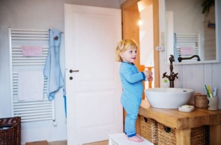 Toddler standing on a stool while brushing his teeth in bathroom