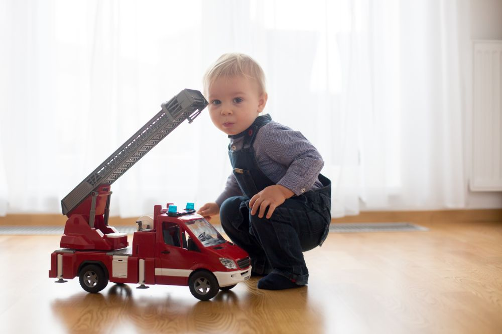 Toddler playing with toy fire truck