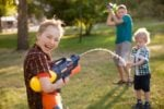 Boys playing with water guns outside