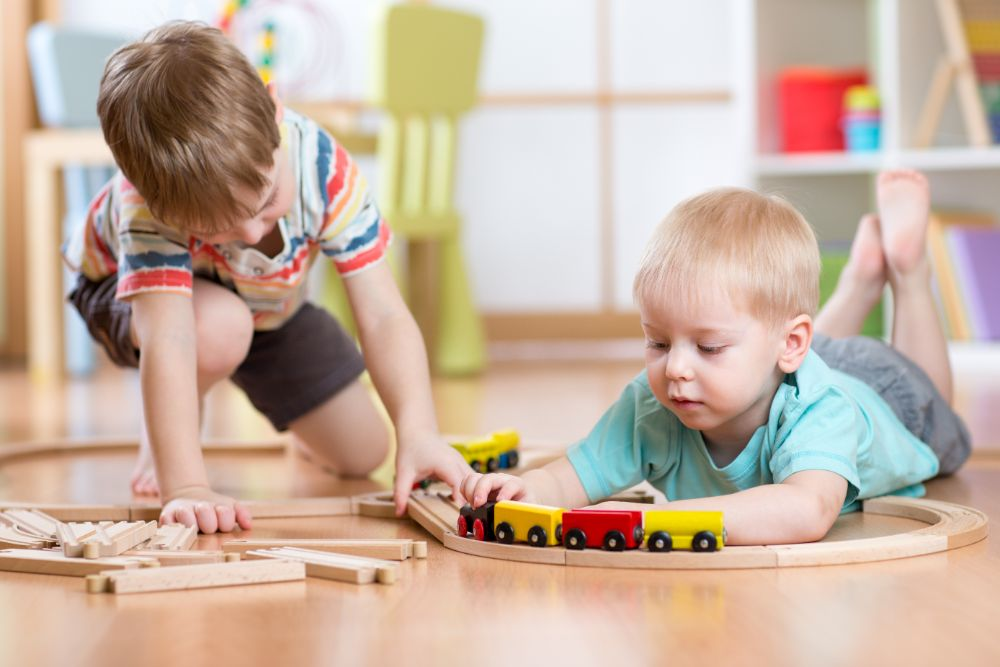 Two little boys playing with wooden train set