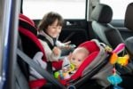 Toddler and baby boy in car seats
