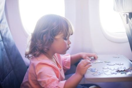 Toddler playing with a puzzle in a plane