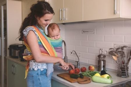 Mom wearing her baby in a carrier while chopping fruits