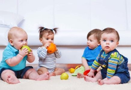 Four babies playing with toys