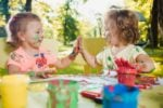 Two little girl painting messily outdoors