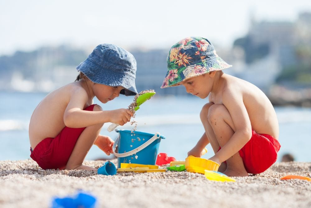Two cute boys playing in the sand