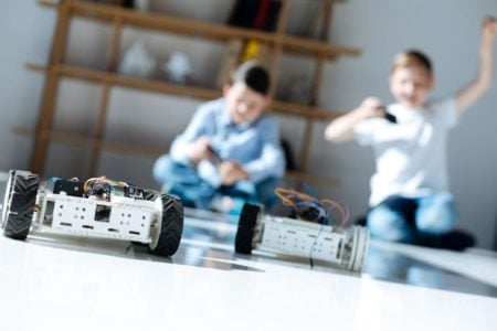 Two young boys racing with robotic cars