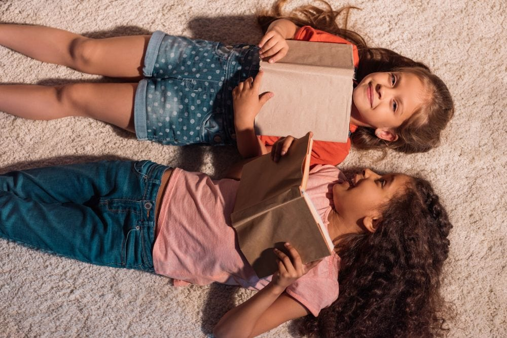 Two young multicultural girls lying on the floor while reading books