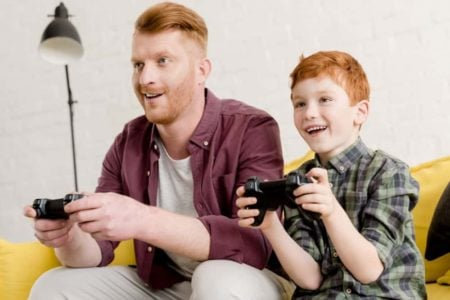 Redhead father and son happily playing video games together