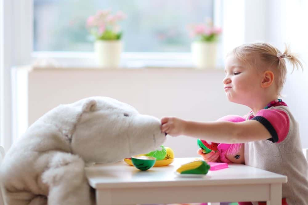 Little girl feeding her stuffed animal toy vegetables