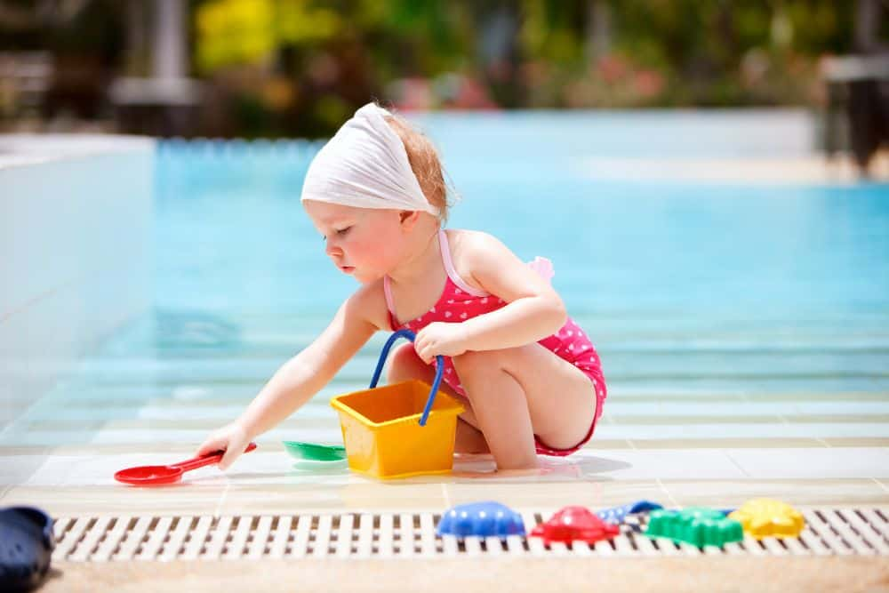 Toddler playing with toy bucket and shovel by the pool