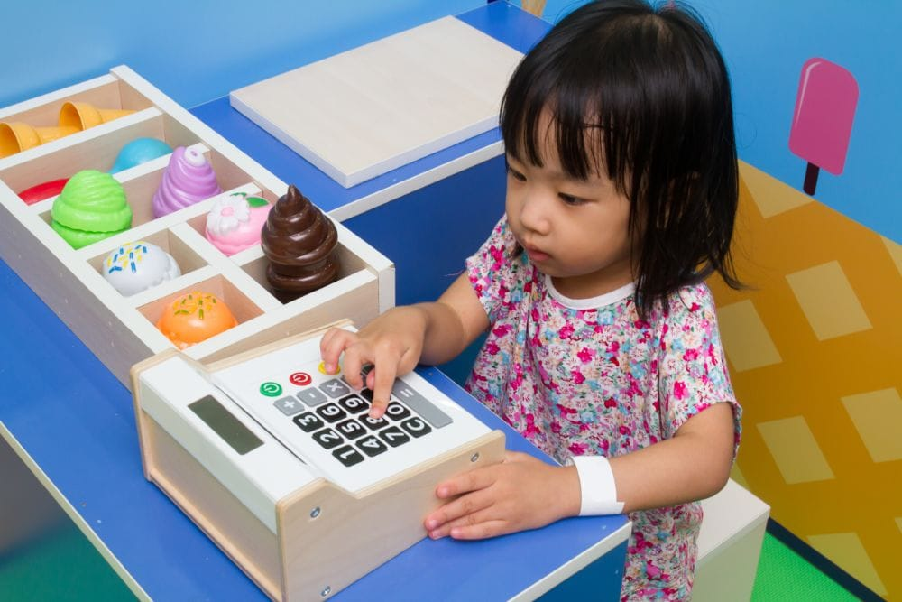 Little asian girl playing with toy cash register