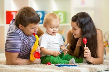 Happy parents and baby playing with musical toys