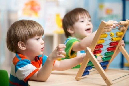Two cute boys playing with abacus toy