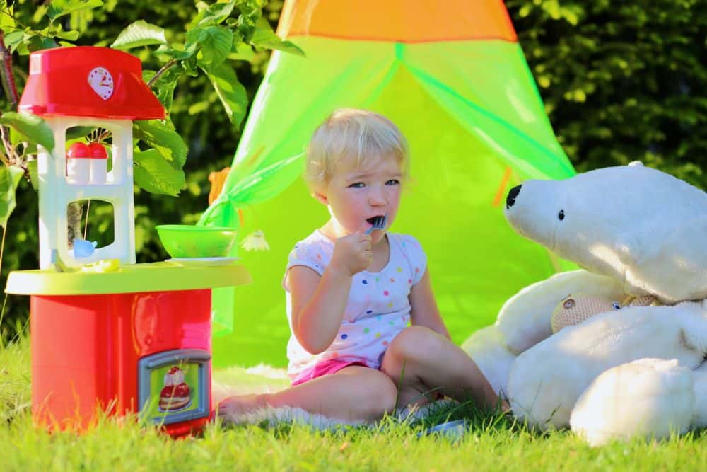 Little girl playing outside with stuffed animal and cooking set
