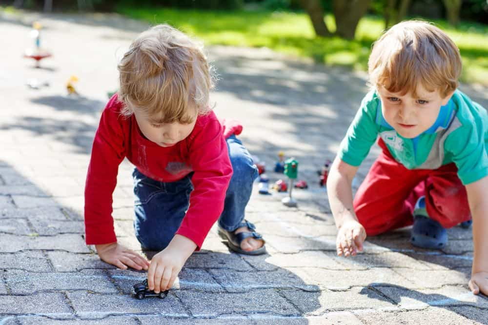 Two young boys playing with toy cars outdoors