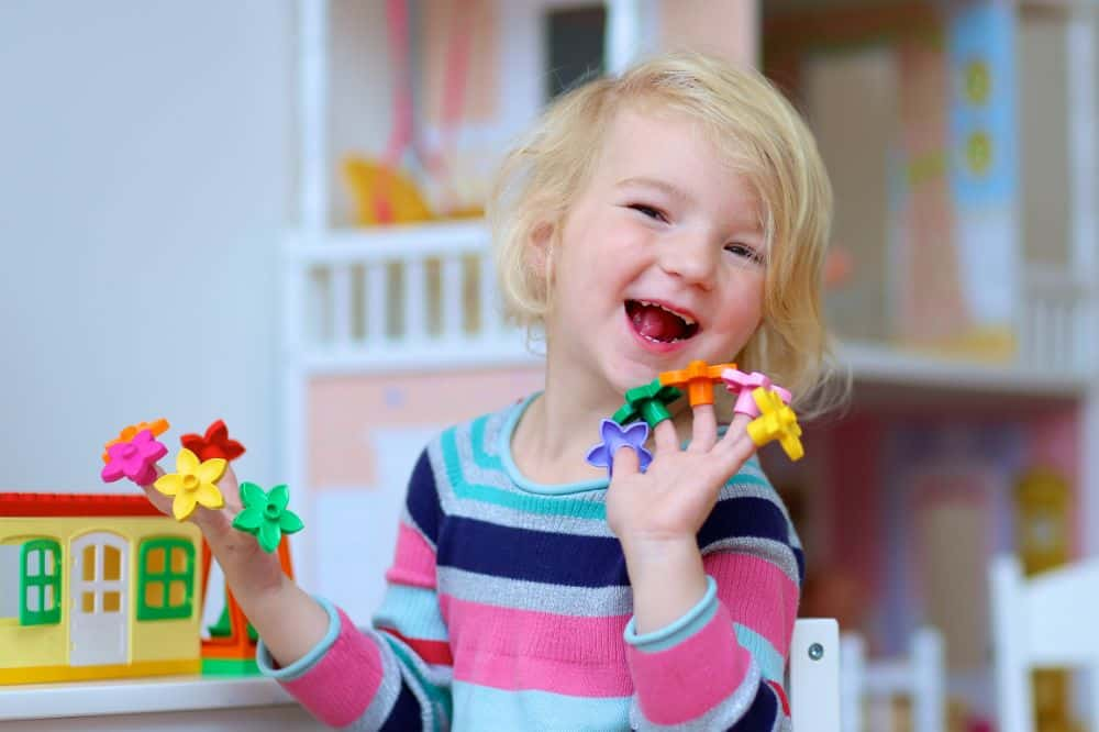 Cute little girl happily playing with flower toys