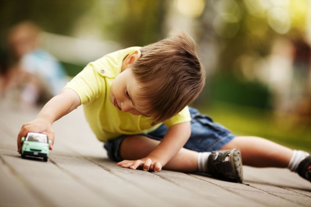 Little boy playing on the ground with a little toy car