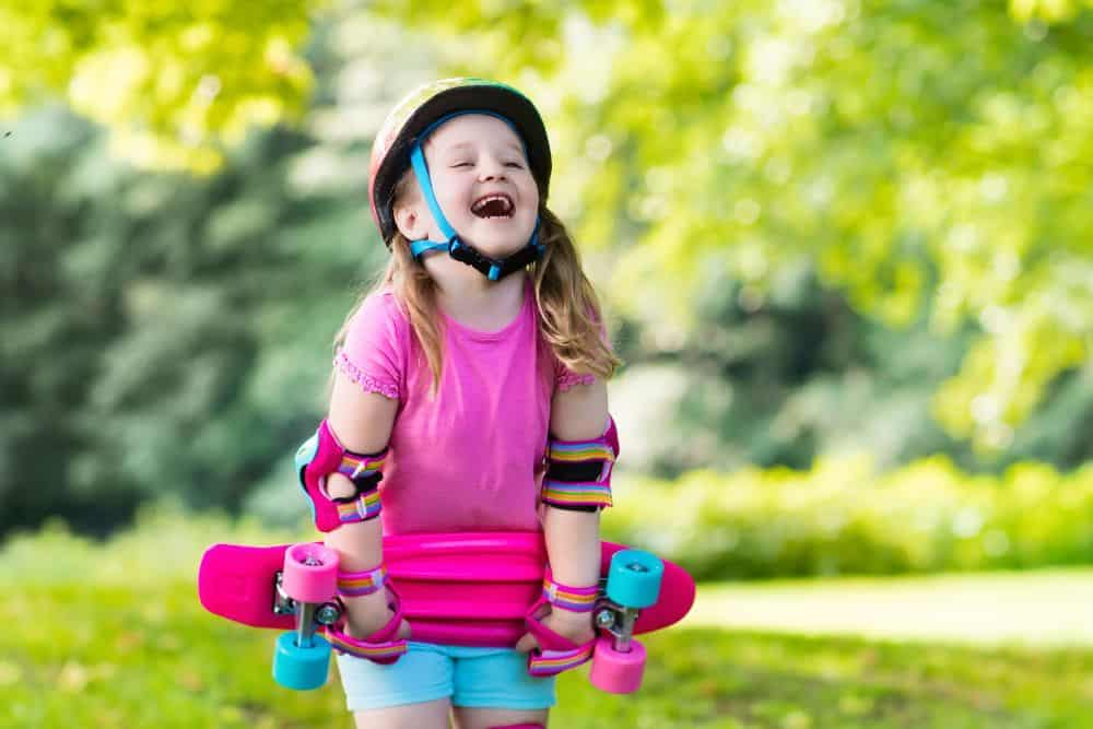 Little girl wearing safety gear while laughing and holding her pink scooter