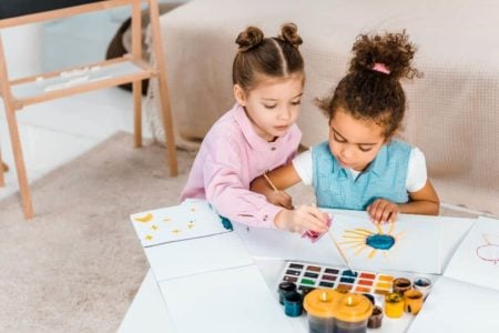Two young multicultural girls painting on the table