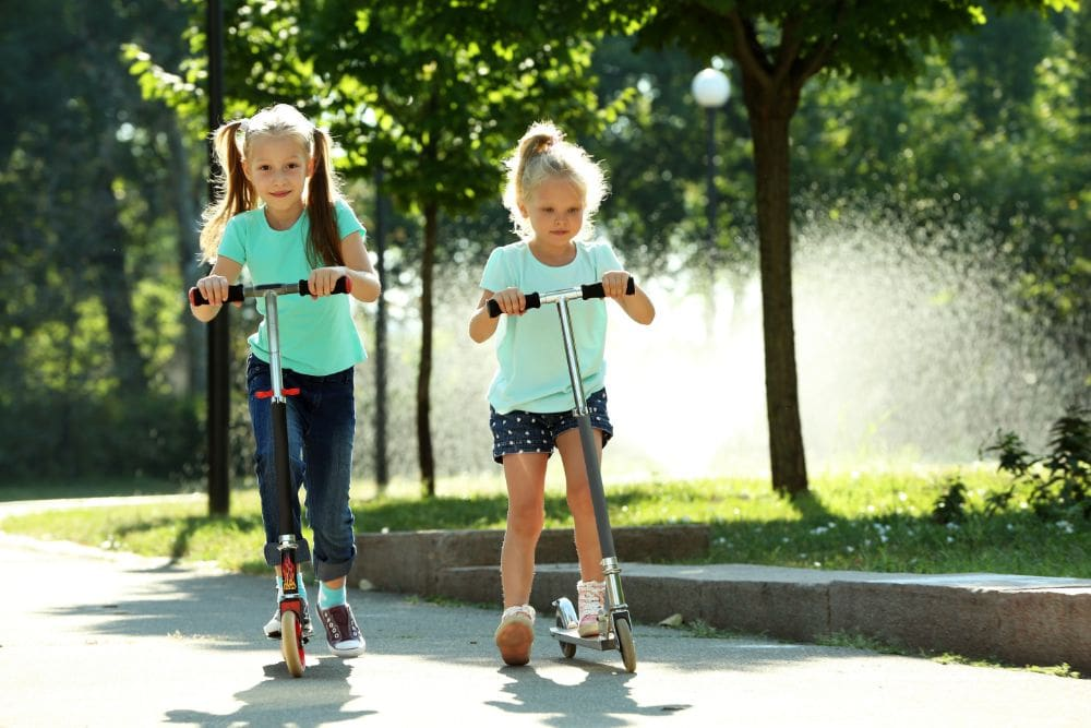Two young girls in green shirts riding their scooters outdoors